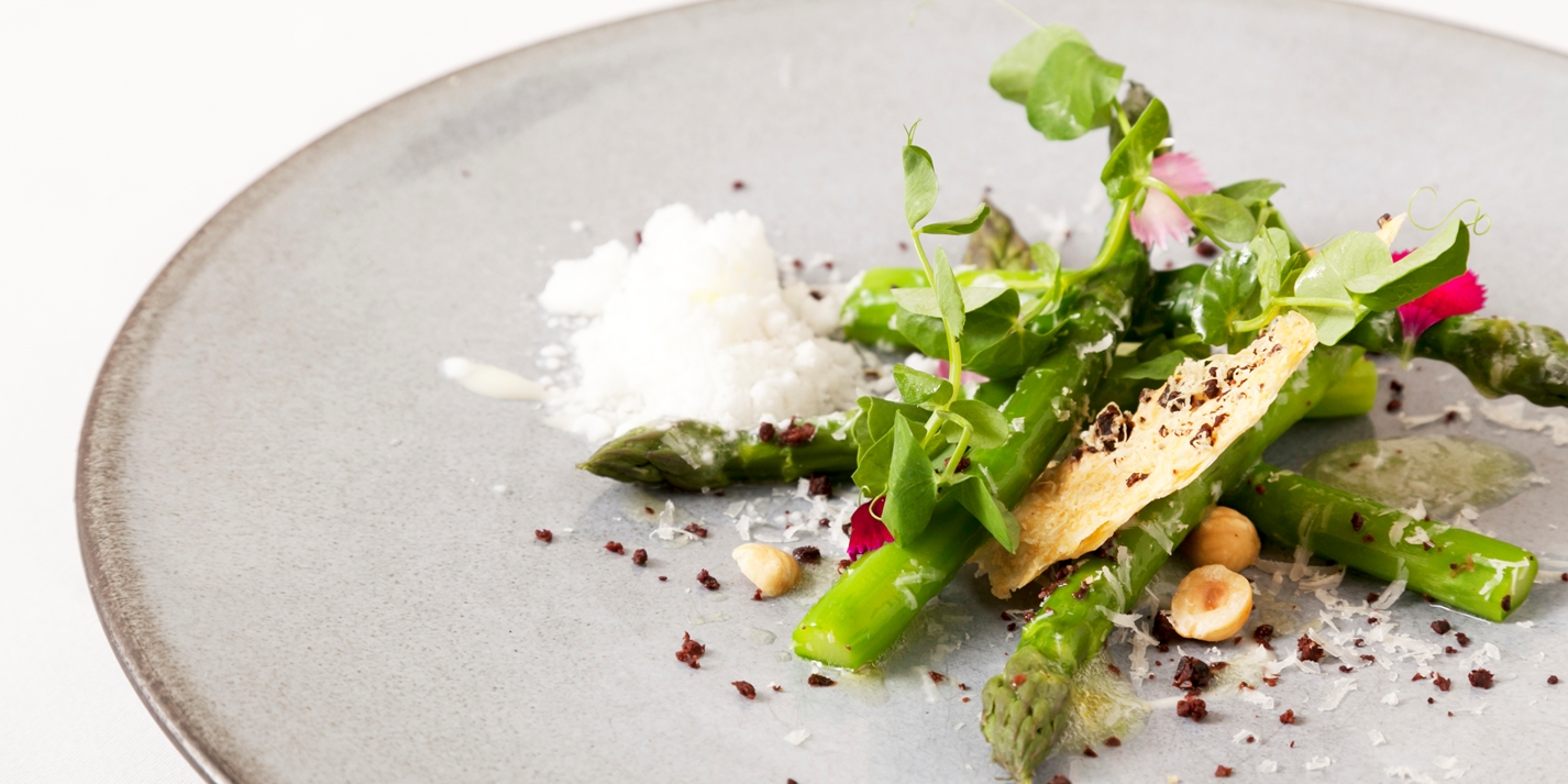 Asparagus with Parmesan snow, olive biscuit and hazelnuts