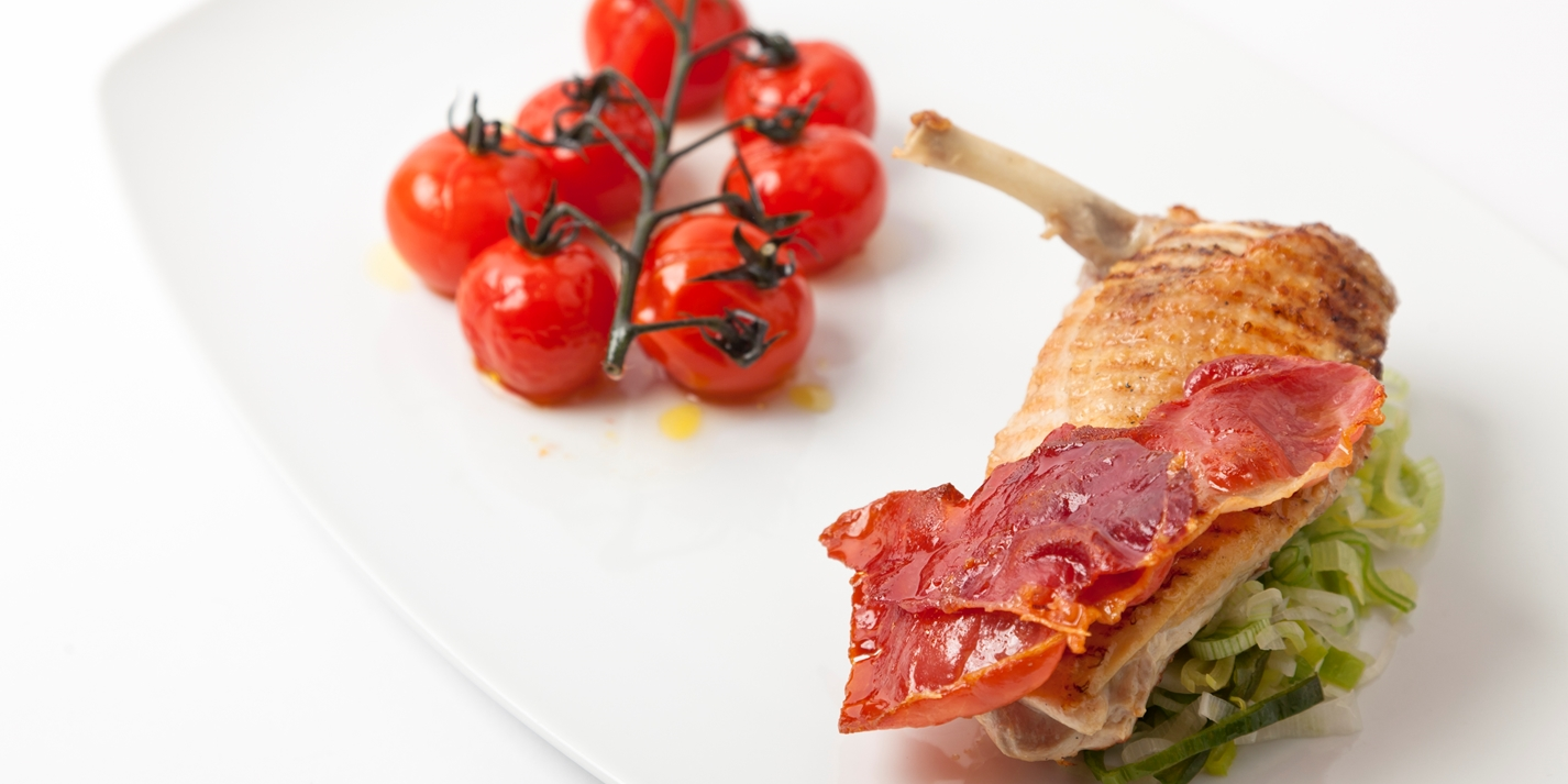 Grilled guinea fowl breast with roasted vine tomatoes and crispy ham