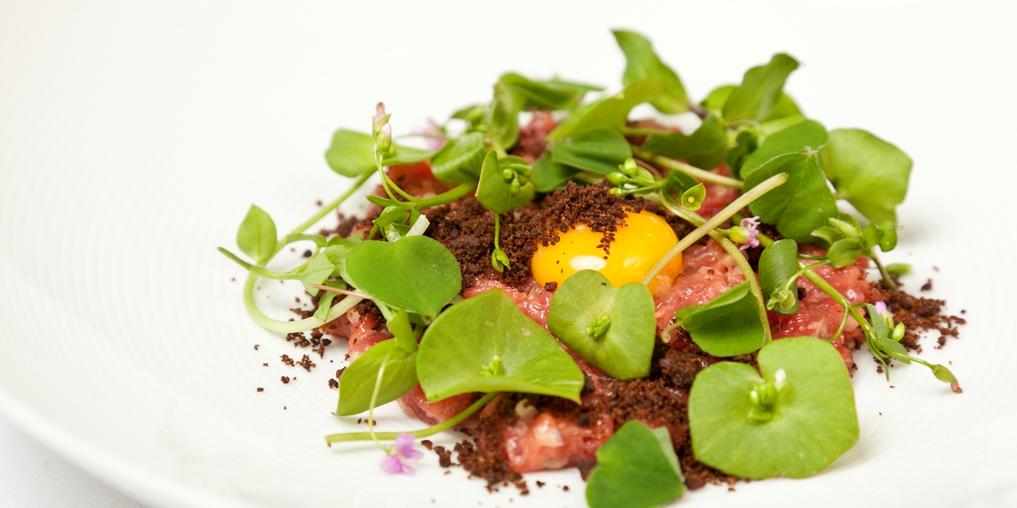 Veal tartare with dark malt crumble, wild herbs and quail eggs