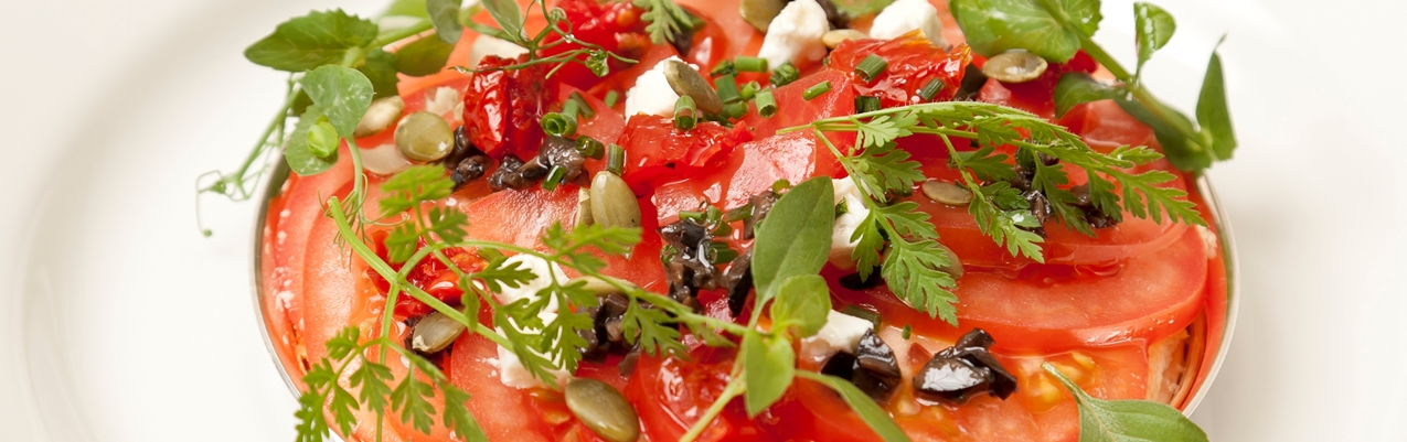 Baked tomato galette with goat's cheese, tapenade and pumpkin seeds