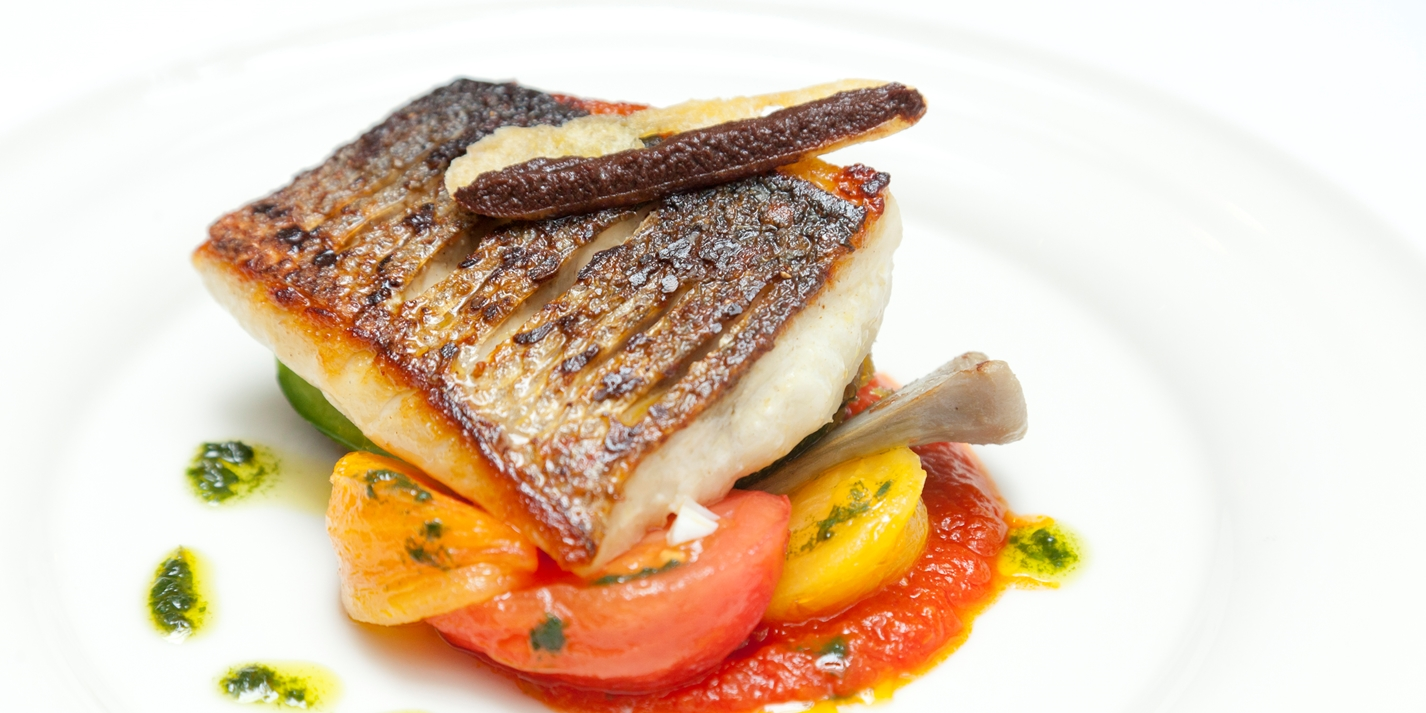 Griddled sea bass with stuffed courgettes, tomatoes, olives and basil