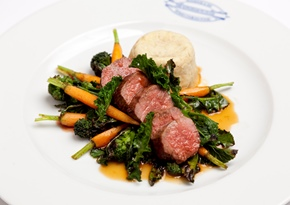 Lamb loin with steamed pudding, charred sprouting broccoli and baby carrots