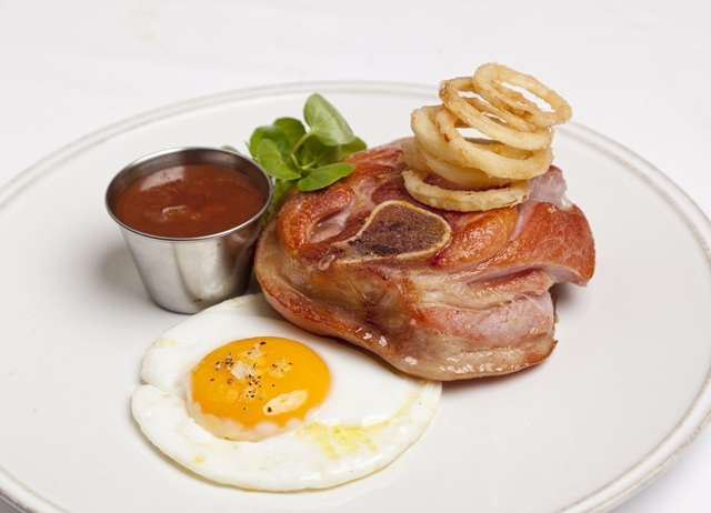 Osso buco of gammon with gooseberry ketchup, fried duck egg and crispy pickled onion rings