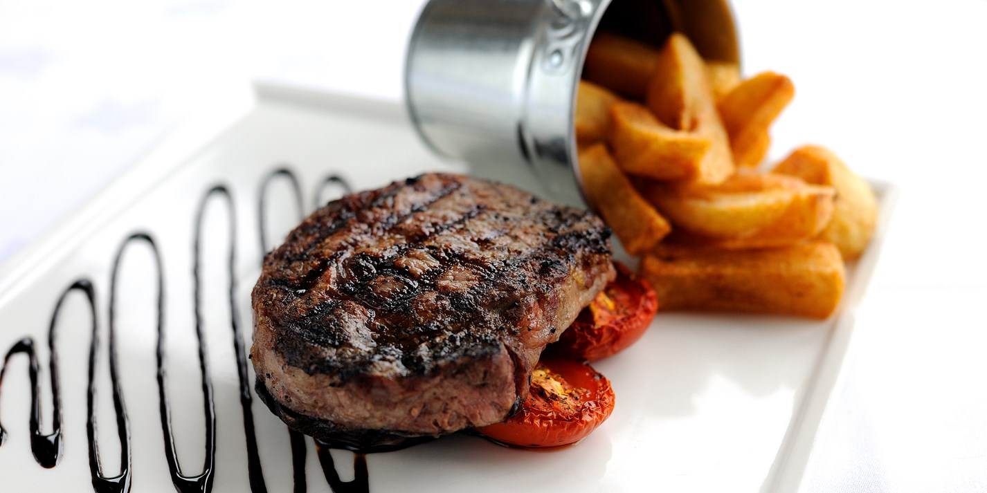 Rib-eye steak with chunky chips, field mushrooms and vine tomatoes