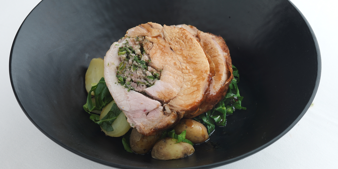 Herb-stuffed pork loin with spring greens and Jersey Royals
