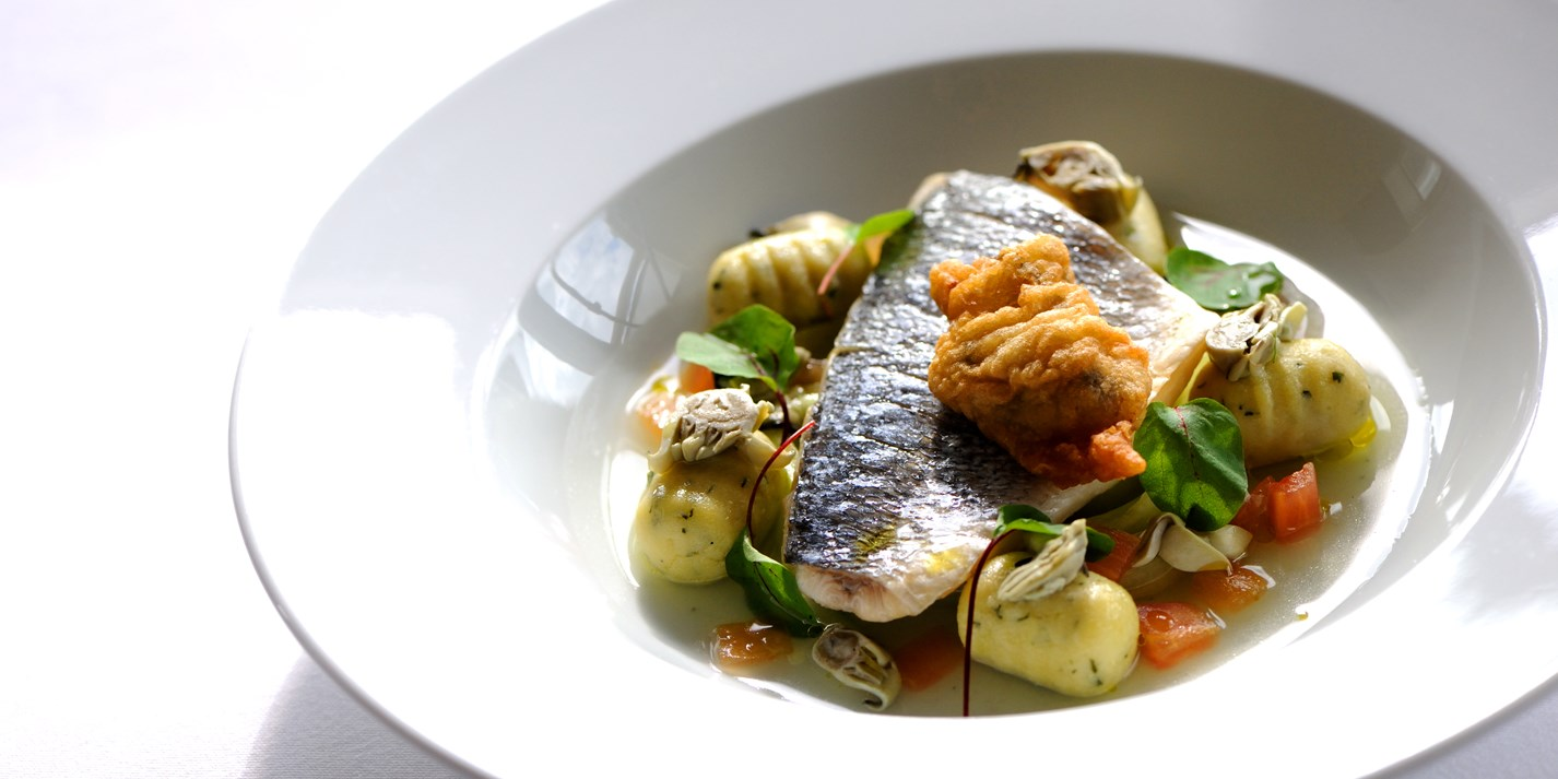 Steamed fillet of sea bream with a nage of Cornish oyster, tomatoes and cucumber and herb gnocchi