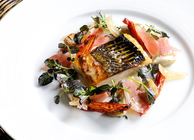 Fillet of sea bass with Parma ham, sauté artichokes and watercress