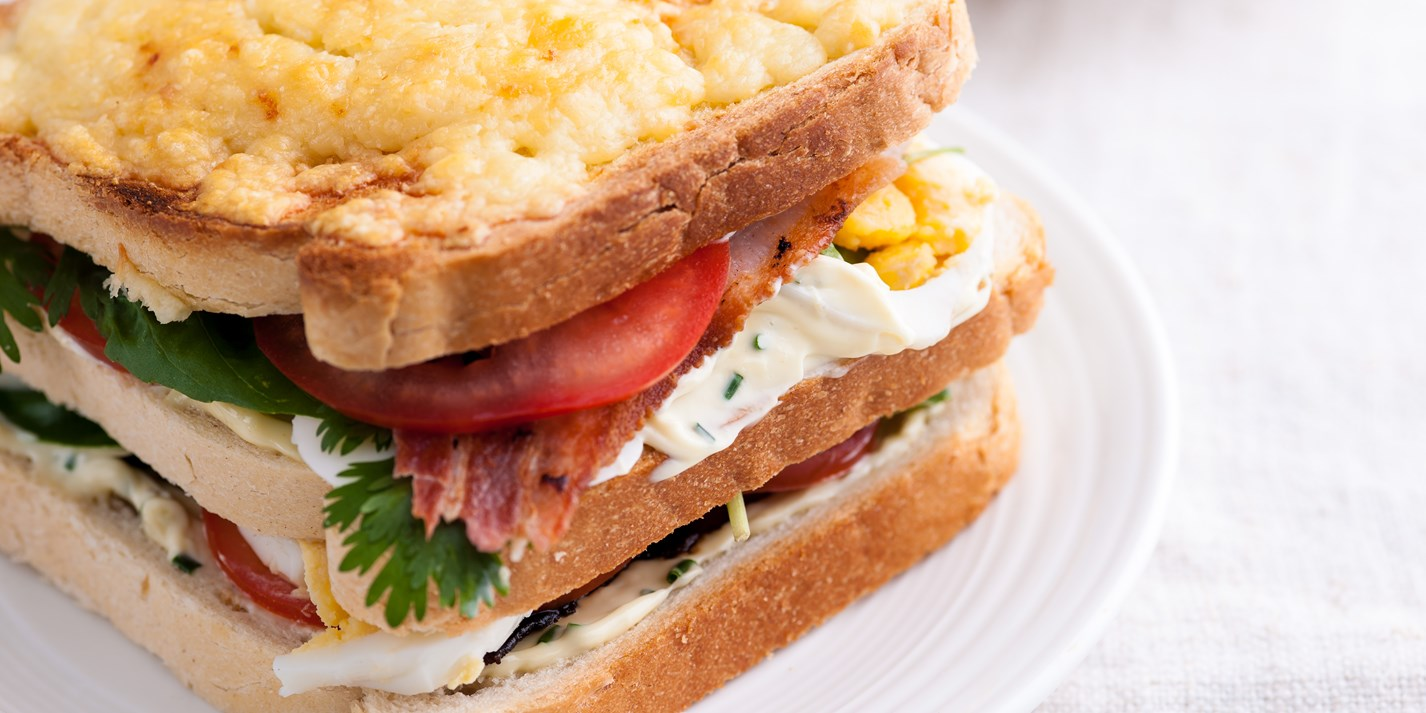 Bacon, egg, tomato and cheddar-garlic mayo club sandwich