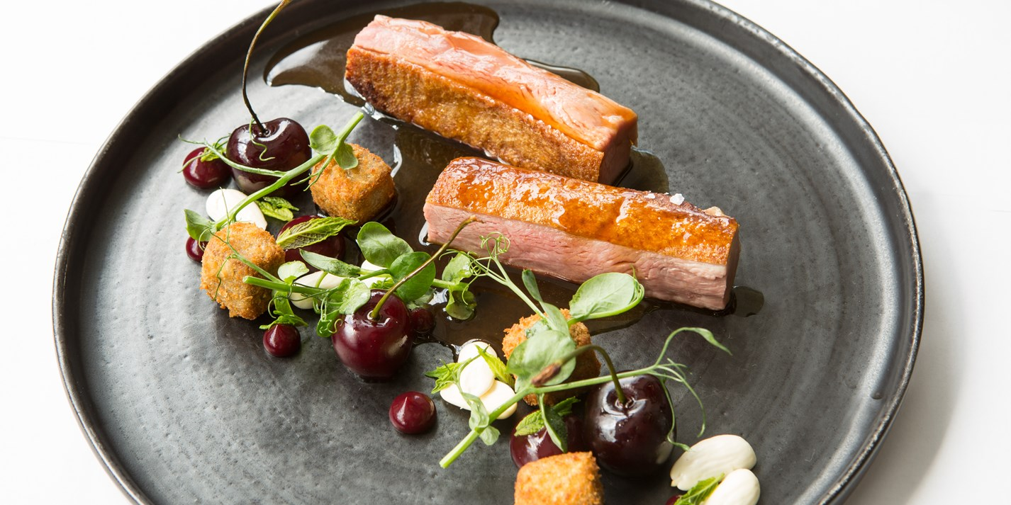 Roast duck breast and crispy leg croquettes with cherries and almonds