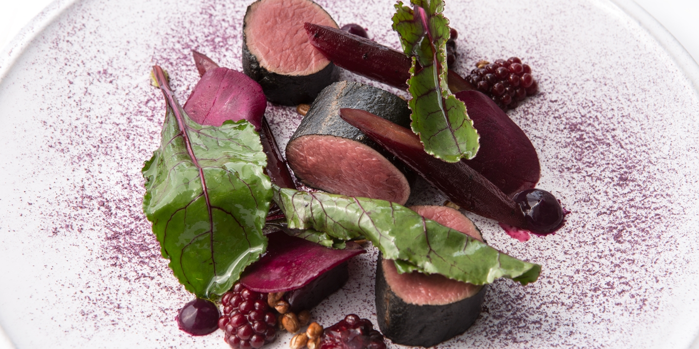 Hay smoked roe deer with red fruits, vegetables and leaves