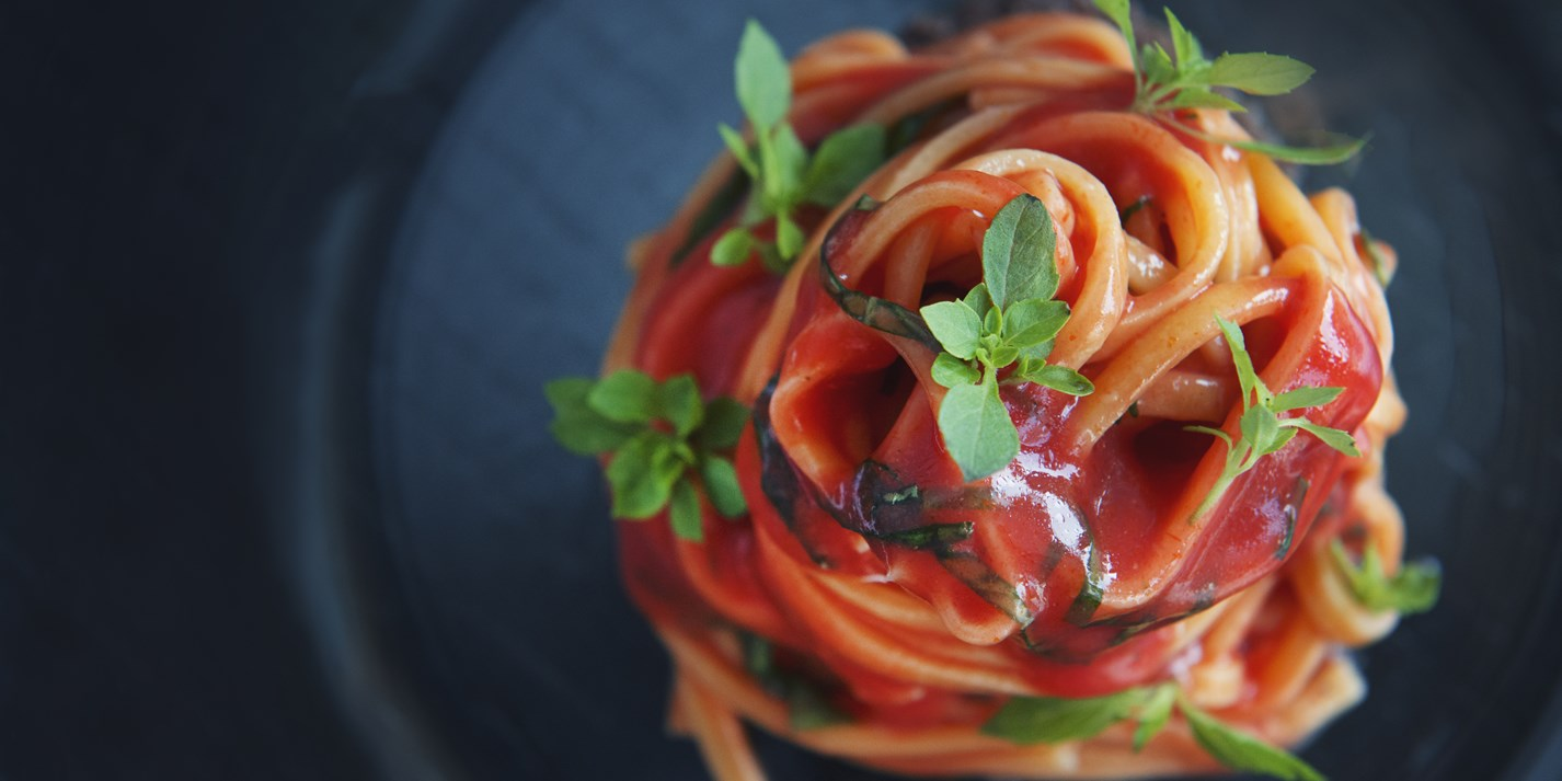 Spaghetti alla chitarra with plum tomato sauce, olives and basil