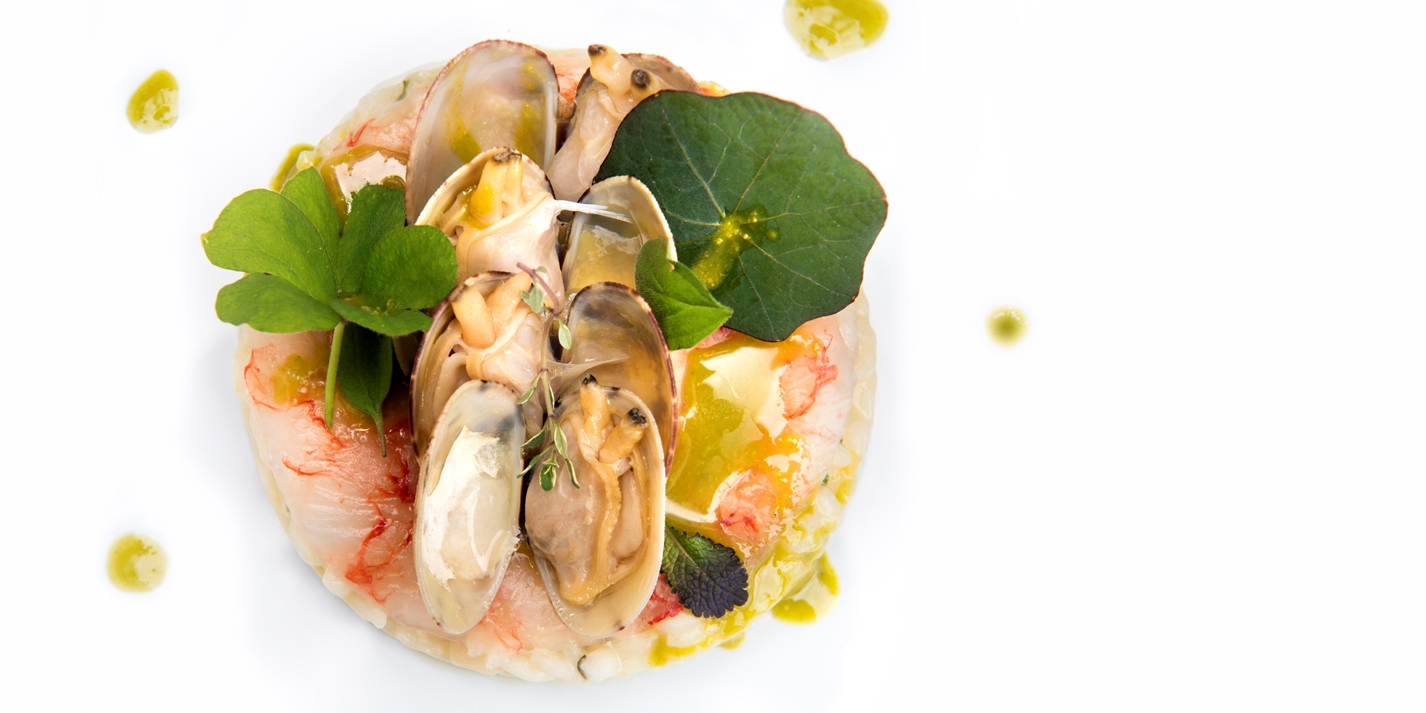 Vialone Nano risotto cremaed with lemon jam, raw prawns, clams and Bronte pistachio oil