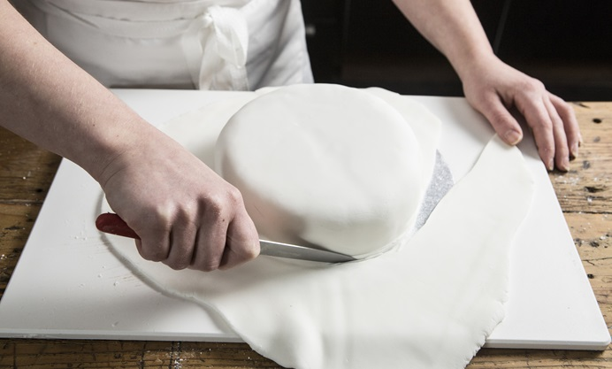 Use a sharp knife to trim away the excess sugar paste
