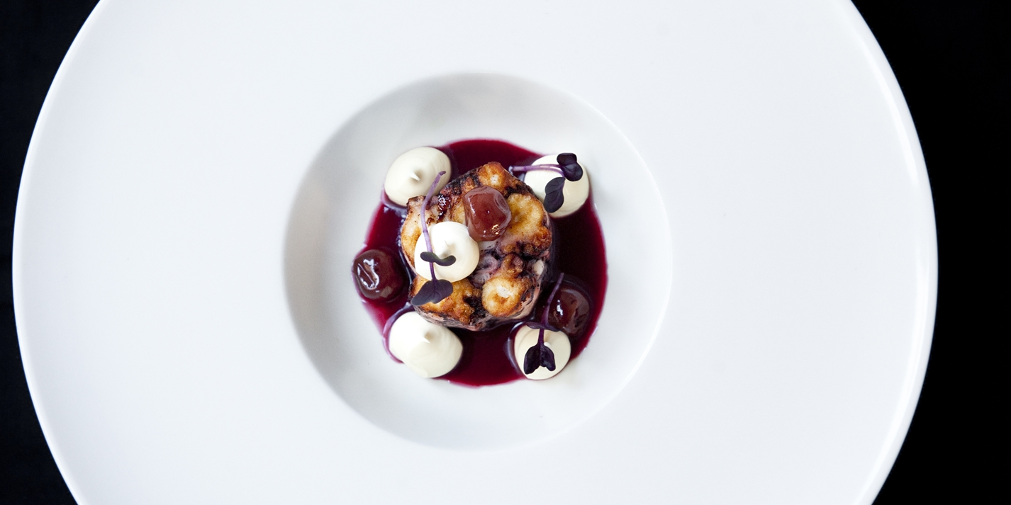 Braised octopus with sour cherries, sour cream and rosemary smoke