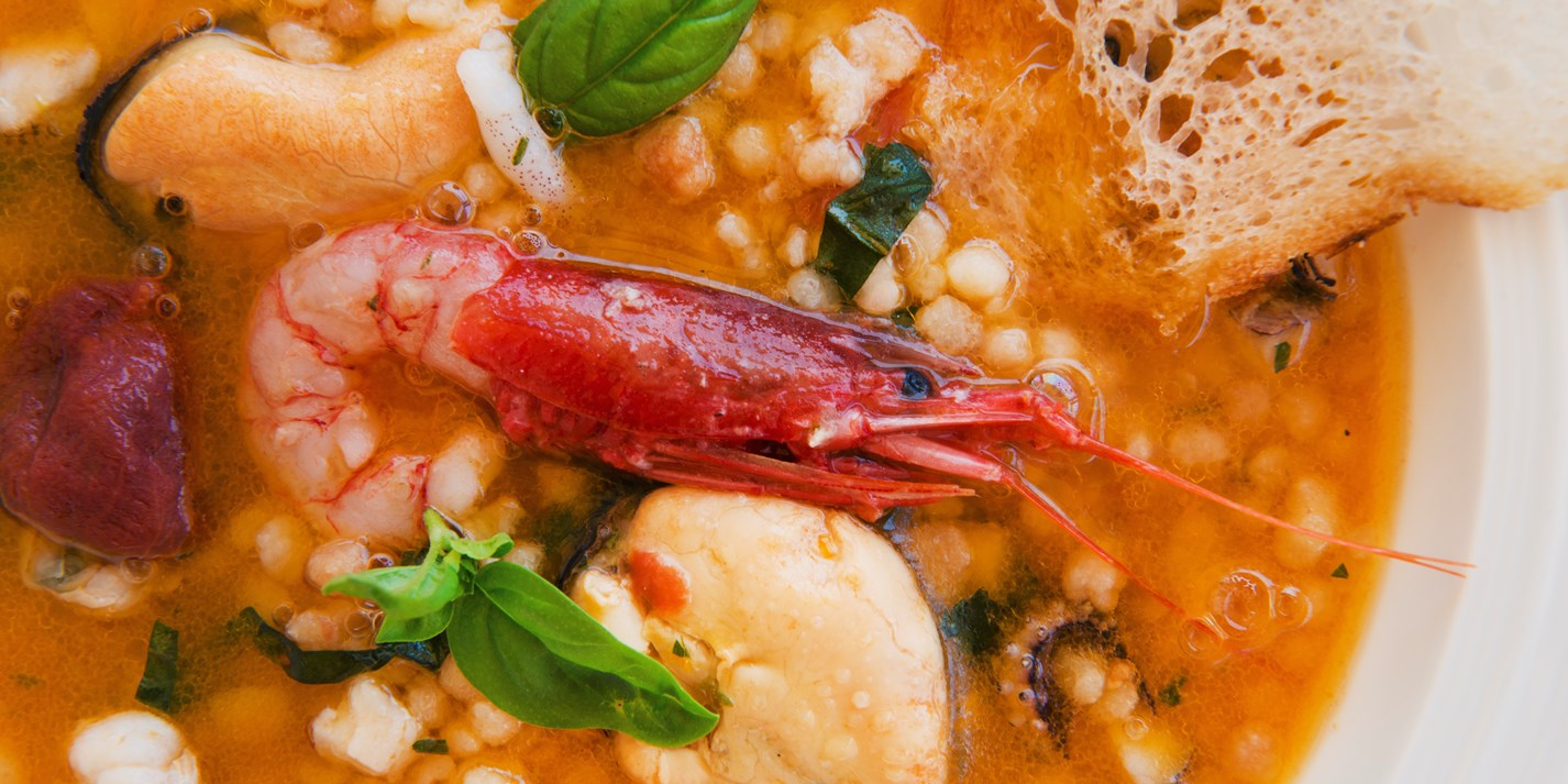 Seafood soup with fregula, basil and citrus