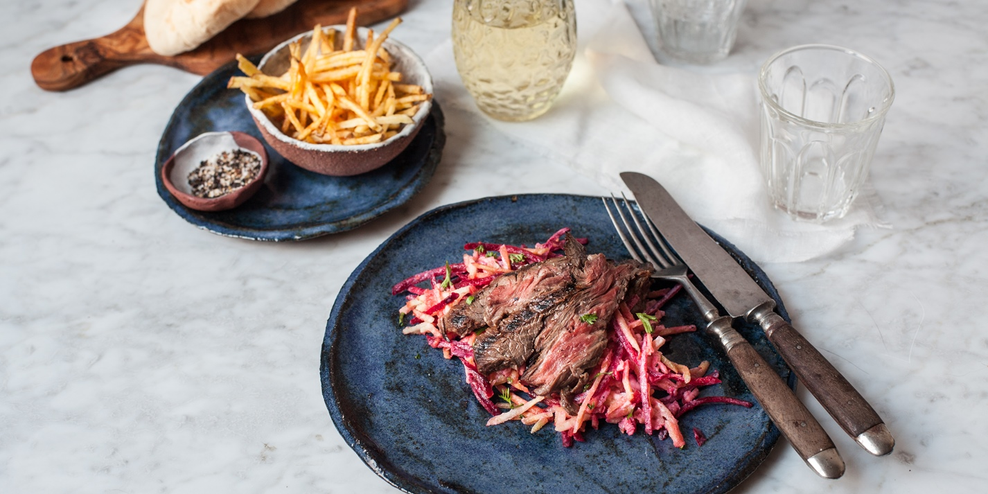 Marinated skirt steak on a fresh roots salad and crispy matchstick fries