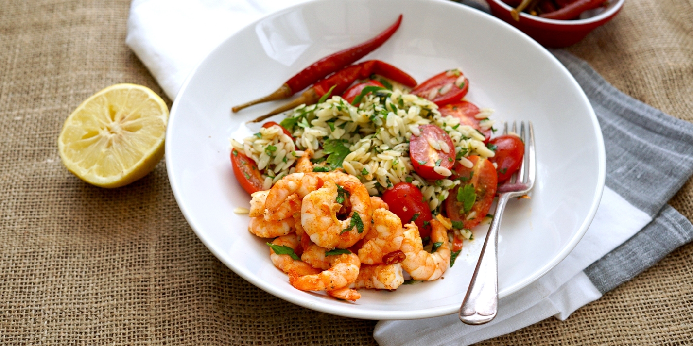 Sizzling prawns in chilli butter with orzo, herb and tomato salad