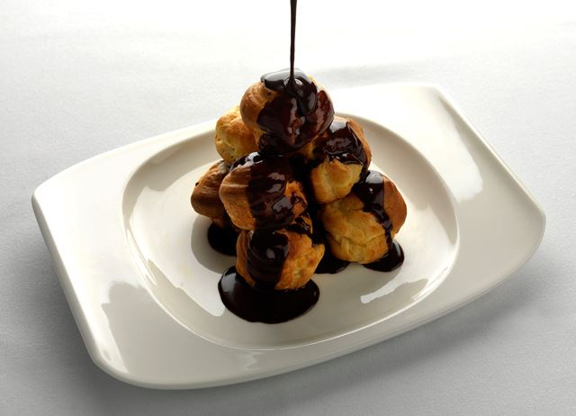 Profiteroles with passion fruit cream and chocolate sauce