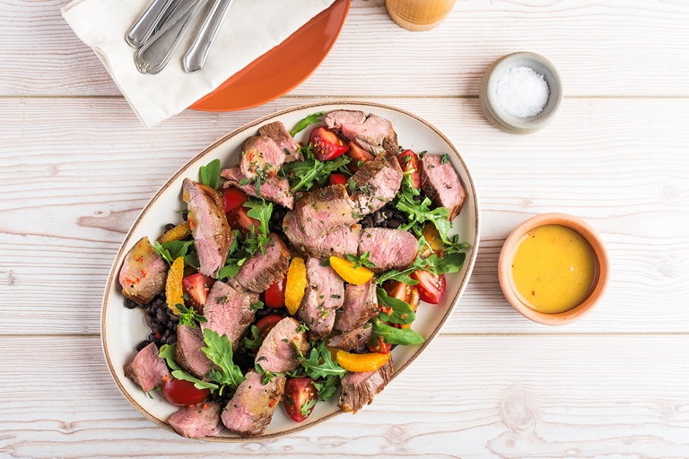 Warm salad of slice lamb leg steak, tomato and black beans with a chilli and orange dressing