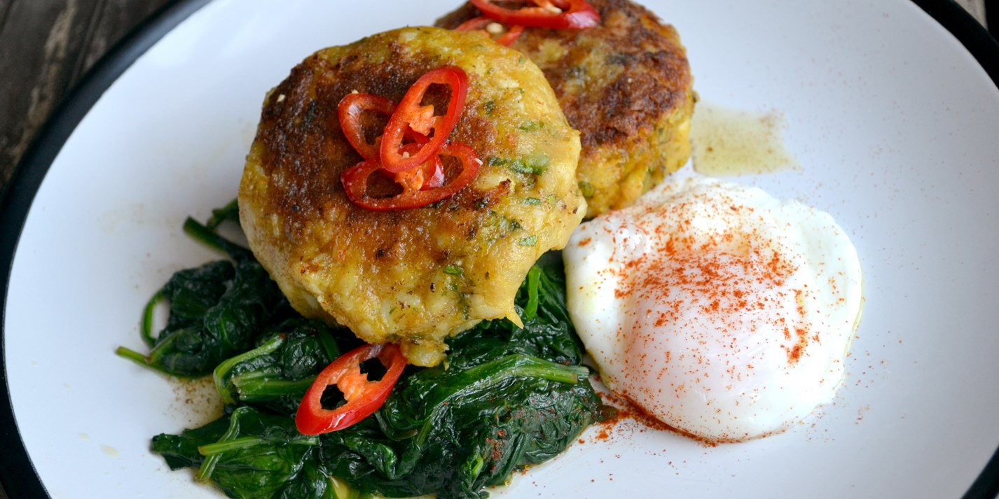 Curried fish cakes with spinach and poached egg