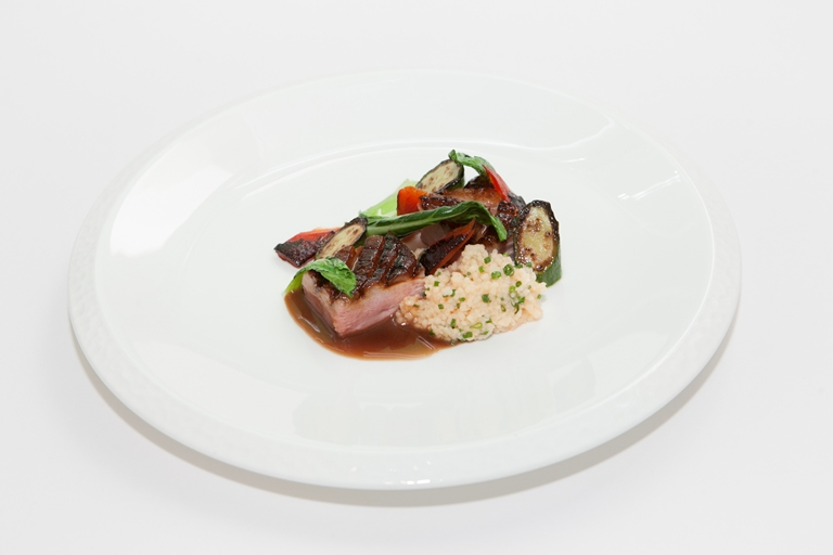 Honey-glazed duck breast, pak choi, baby courgette and tomato couscous