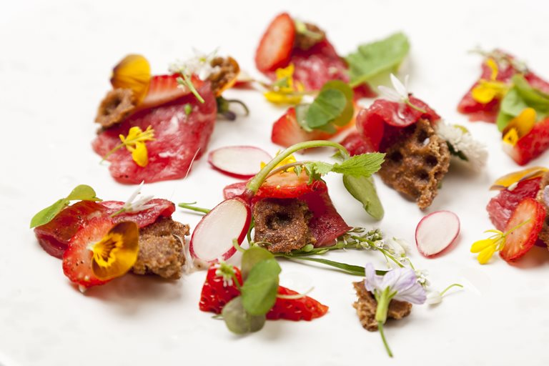 Carpaccio of beef with pickled strawberries, wild spicy leaves and ryvita