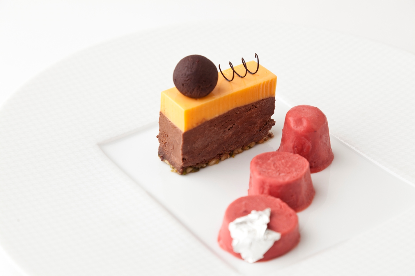 Whisky truffle, dark chocolate-chikki delice, orange mousse and cranberry kulfi
