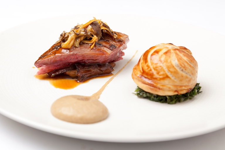Roast wood pigeon with pithivier of leg, creamed curly kale and roast Jerusalem artichokes