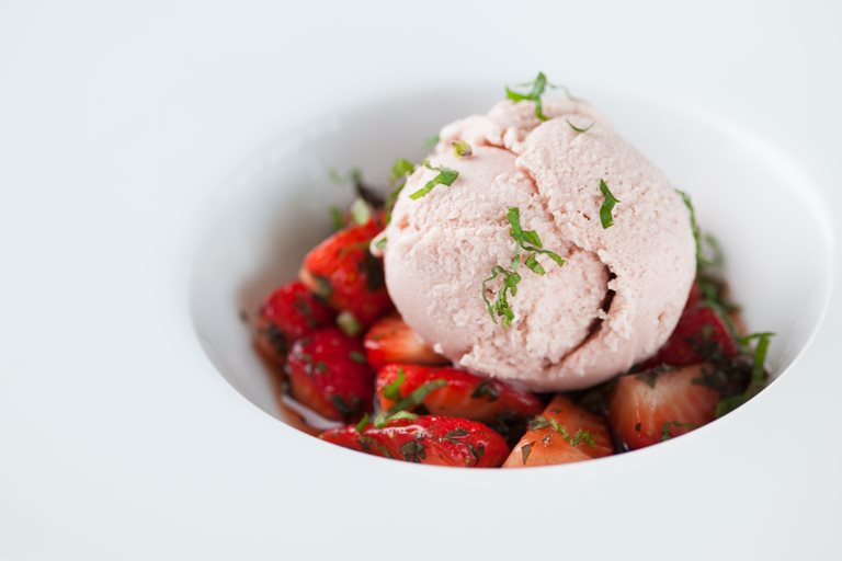 Strawberry ice cream with marinated strawberries and pouring cream