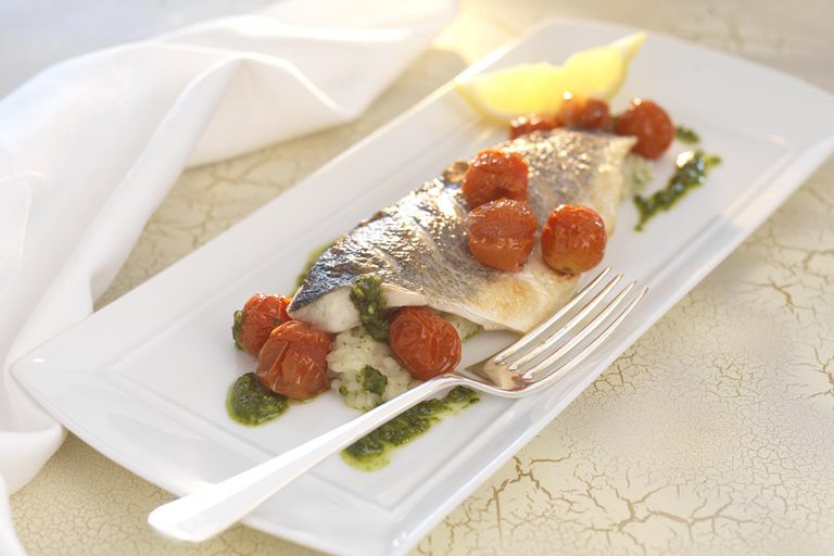 Grilled fillets of sea bass with herb risotto, roasted cherry tomatoes and pesto