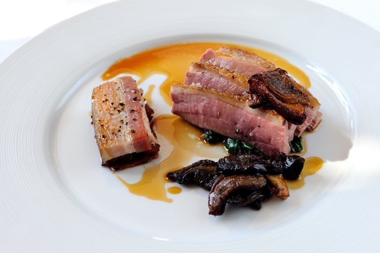 Honey-roasted breast of duck with smoked belly of pork, caramelised endive and ceps
