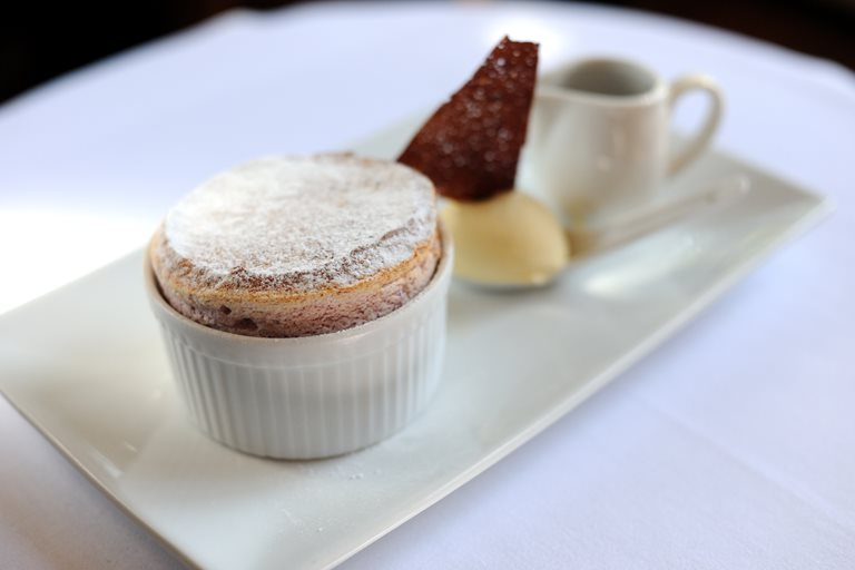 Dark cherry soufflé with clotted cream ice cream and dark chocolate sauce