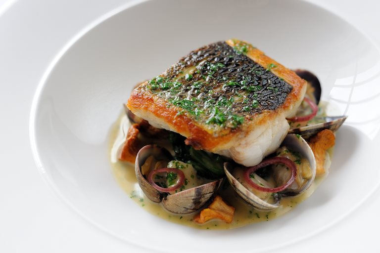 Pan-fried sea bass, butter spinach, clams, poached cod cheeks and fish sauce
