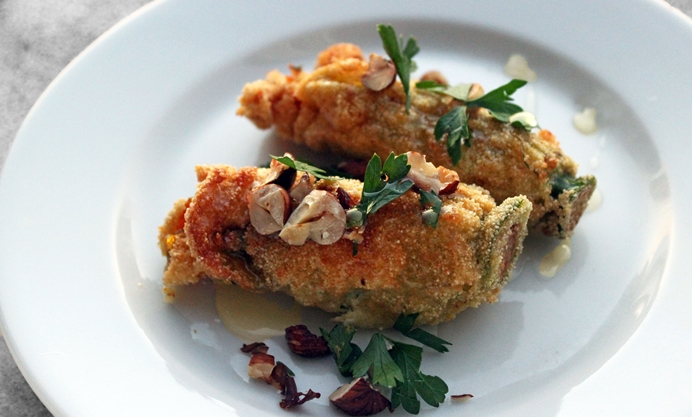 Plate the courgette flowers with the toasted hazelnuts