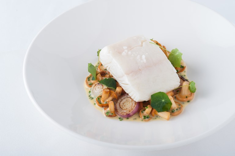 Vin jaune poached halibut with girolles and grilled grelot onions