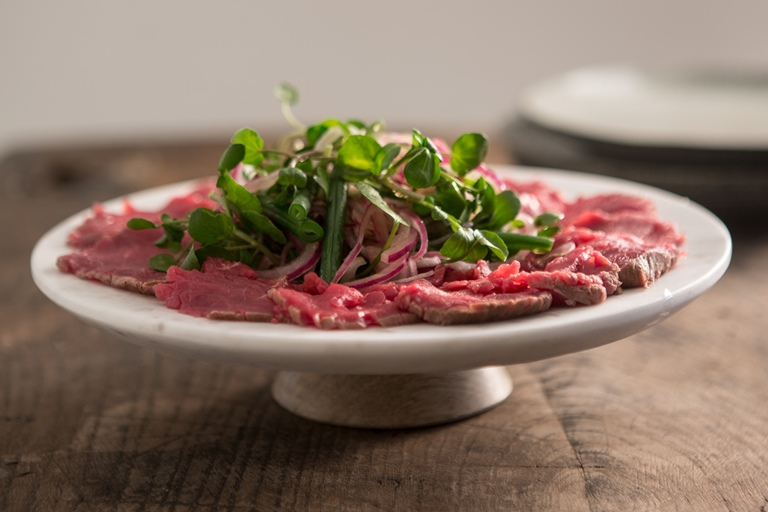 Carpaccio of beef with a sweet and sour onion and green bean salad