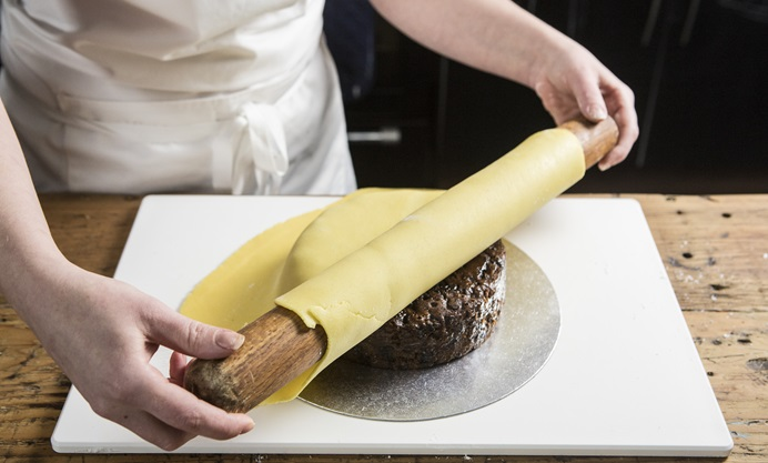 Fold the marzipan over the rolling pin and lay on to the cake