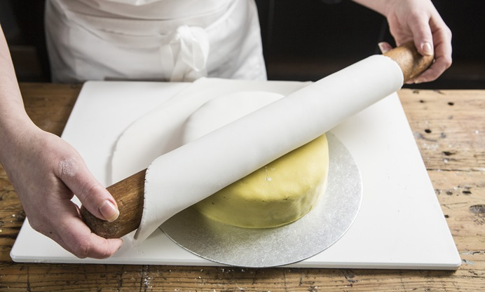 Fold the sugar paste over the rolling pin and lay onto the cake