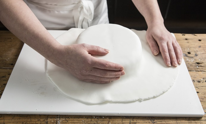 Run the palm of your hand around the cake, ensuring that there are no creases.