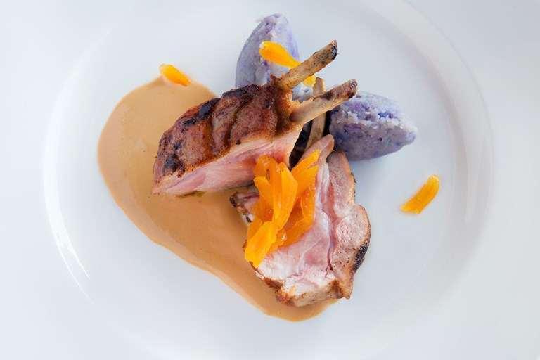 Rack of piglet with purple potatoes, dried apricots and garlic sauce