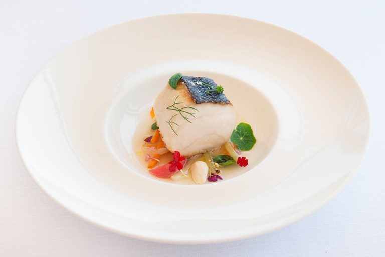 Roasted amberjack with cooked vegetable salad, fresh almonds and tomato water