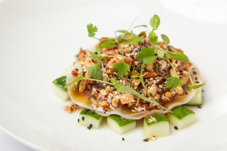 Pulled pork and chorizo 'raviolo', pickled cucumber, sesame, peanut and green chilli