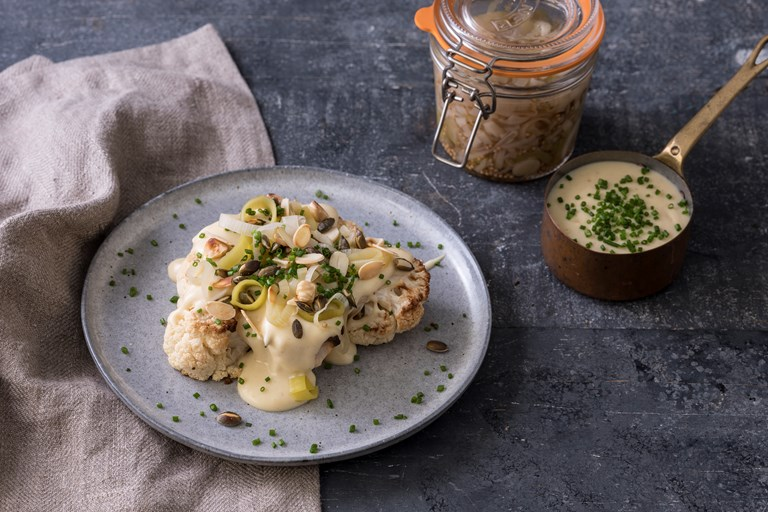Roast cauliflower with smoked cheddar sauce, pickled leeks, nuts and seeds