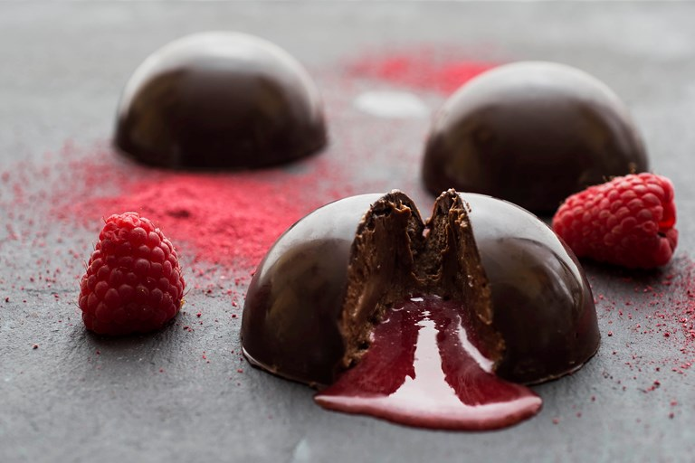 Chocolate mousse domes with raspberry coulis centre