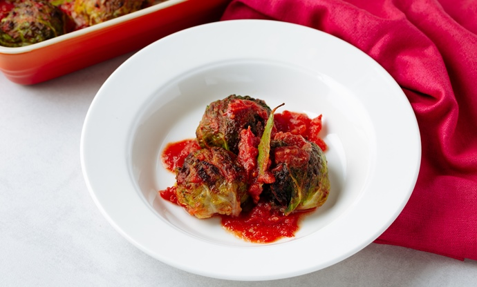 Stuffed beef and cabbage parcels, rice, onion and tomato sauce