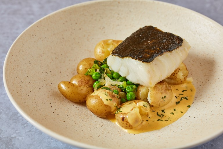 Baked cod with pea and lettuce fricassee, potatoes and mint Hollandaise