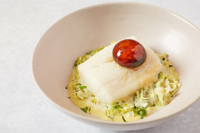 Poached haddock with stewed leeks, soy-cured egg yolks and curry dressing