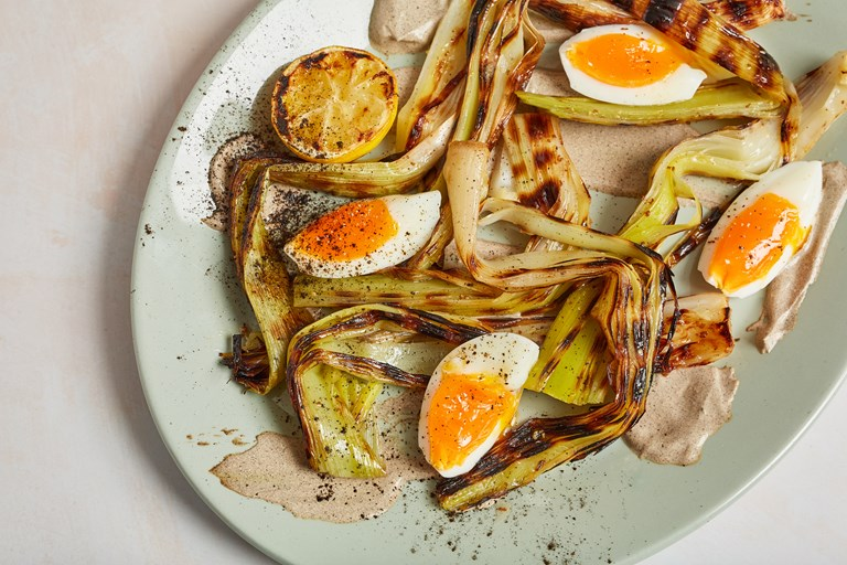 Charred leeks with leek ash crème fraîche, burnt citrus dressing and soft egg