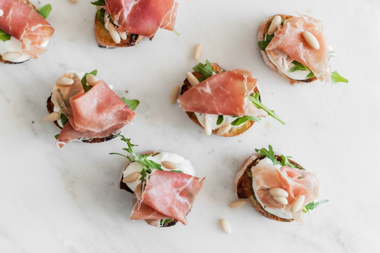 Crostini with rocket, buffalo stracciatella, Prosciutto di Parma and pine nuts