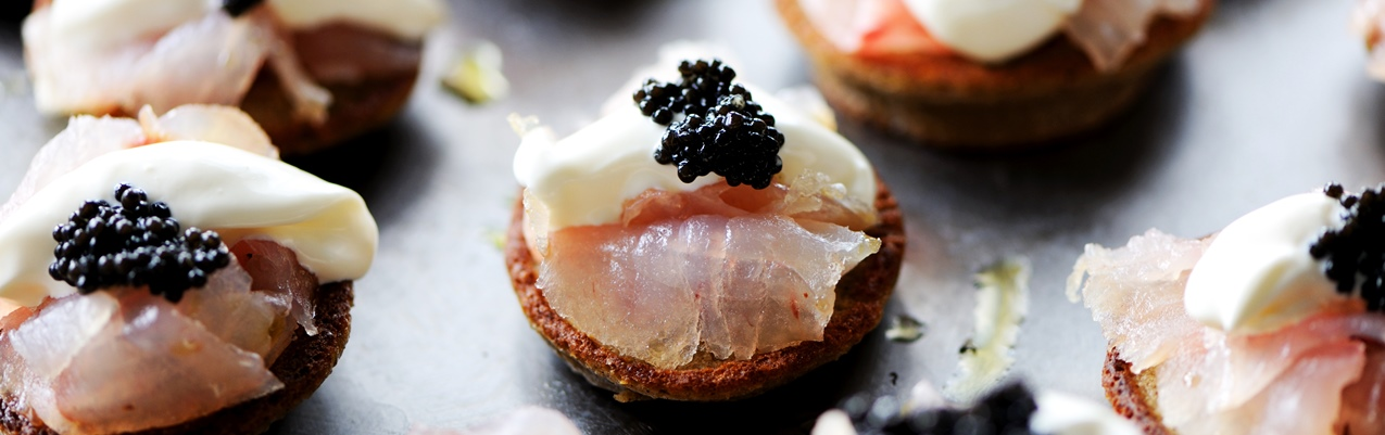 Citrus-cured sea bass on blinis with ossetra caviar and crème fraiche